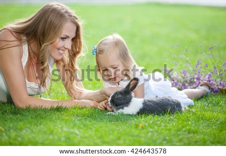 Young woman and her daughter playing with a pet rabbit in a park - stock photo