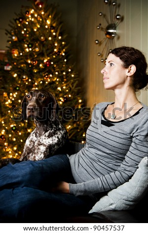 Young woman and her dog at Christmas time.  Focus is on dog's face. - stock photo