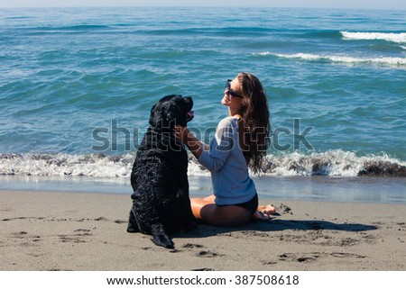 young woman and her dog enjoy on sandy sea beach sunny summer day - stock photo