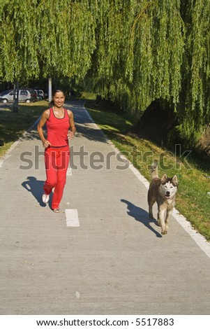 Young woman and her dog running in the morning. - stock photo