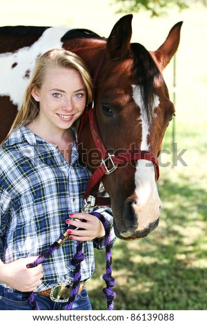 Young woman and her horse - stock photo