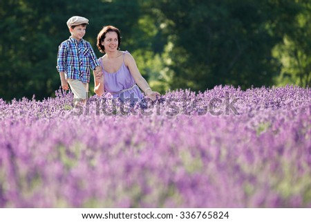 Young woman and her little son in lavender field  on beautiful summer day - stock photo