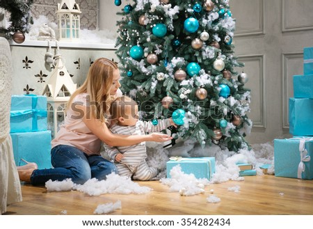 Young woman and her little son touching baubles on Christmas tree - stock photo