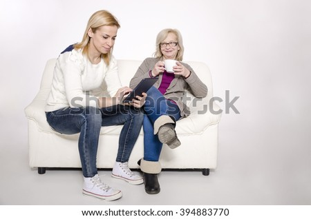 Young woman and her mother sitting on a white couch.