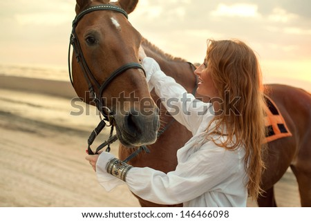 Young woman and horse on sea cost - stock photo