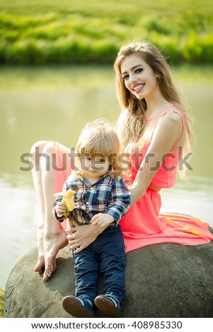young woman and little boy sitting on stone near water sunny day, family life