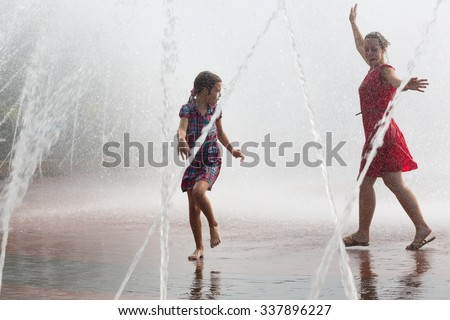 Young woman and little girl are dancing into the fountain.