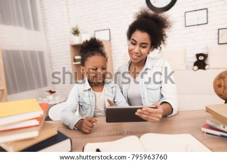 Young woman and little girl are looking at the tablet. They talk to someone on the Internet. This is my mother and daughter.