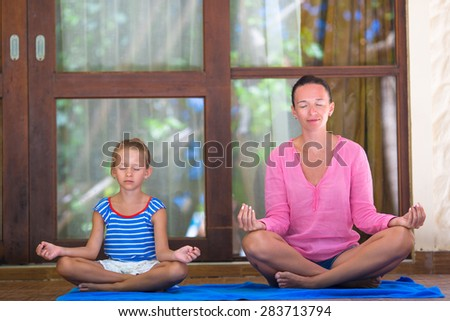 Young woman and little girl engaged in fitness outdoor on terrace - stock photo