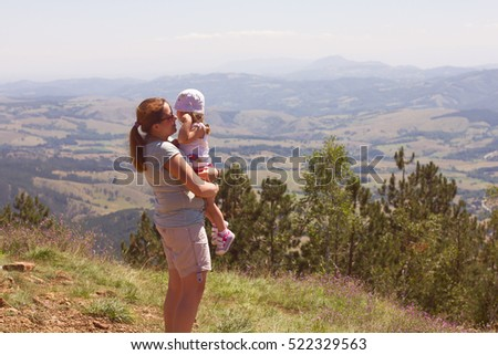 Young woman and little girl enjoying of beautiful nature landscape.