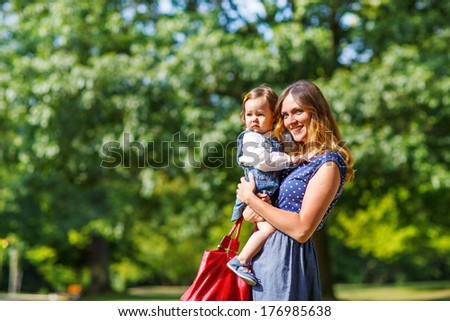 Young woman and little girl of one year walking through summer park - stock photo