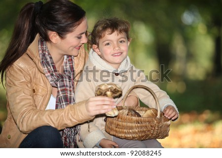 Young woman and little girl with basket of mushrooms - stock photo