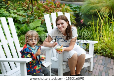 Young woman and little toddler boy eating ice cream, outdoors - stock photo