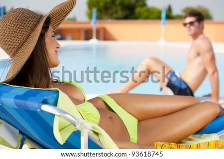 Young woman and man at swimming-pool