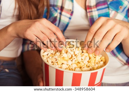 young woman and man  eating popcorn in the cinema - stock photo