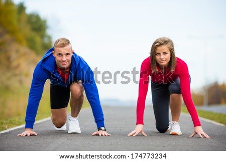 Young woman and man exercising - stock photo