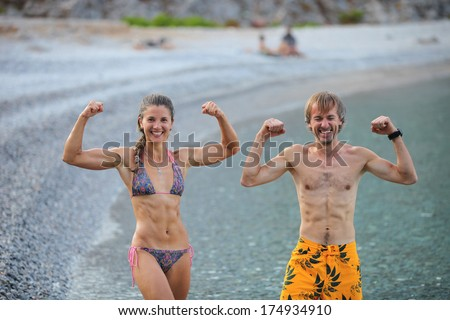 Young woman and man flexing their muscles jokingly while resting at beach - stock photo
