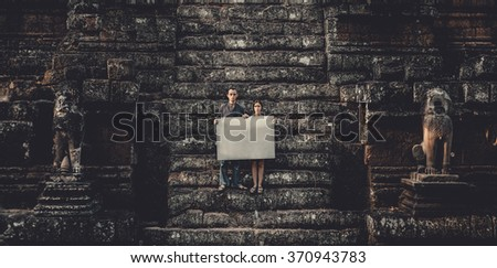 Young woman and man holding blank placard in dark mystic location