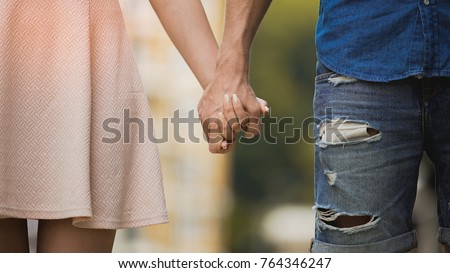 Young woman and man holding hands, tender relationship of sweet couple, love
