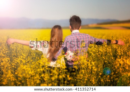 young woman and man in a rapeseed field. Young and joyful. Low key, dark background, spot lighting, and rich Old Masters - stock photo