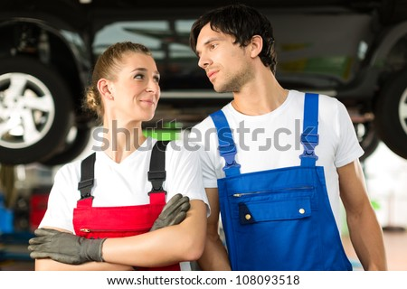 Young woman and man in blue overall - mechanic - stand with in front of a jacked car in a service station - stock photo