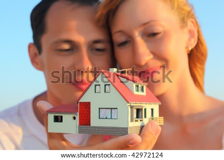 Young woman and man keeping in hands model of house with garage - stock photo