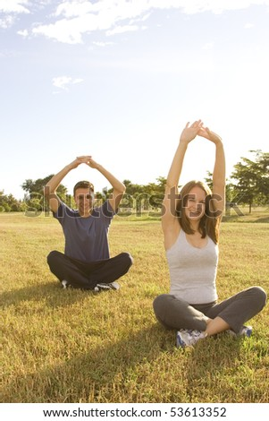Young woman and man outside in a fitness pose - stock photo