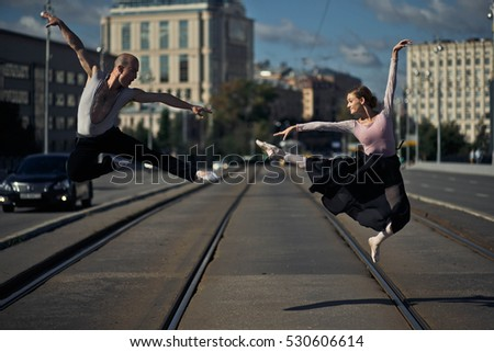 young woman and man performing gymnastic exercises on the road