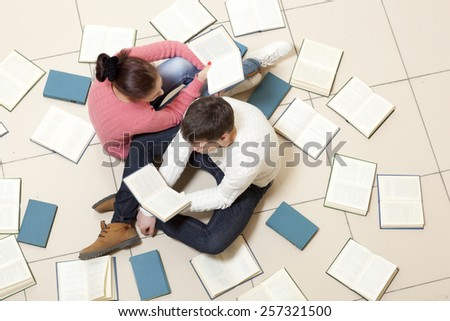 Young woman and man reading a book, top view. Blurred text is unreadable - stock photo