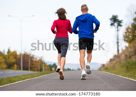 Young woman and man running