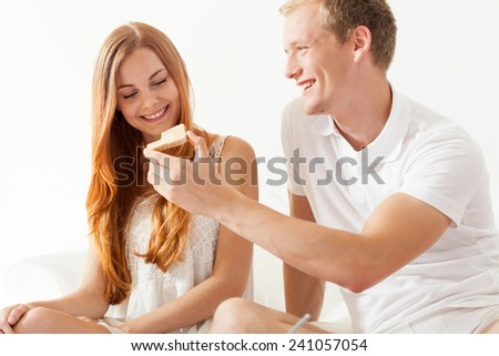 Young woman and man sharing toast on breakfast