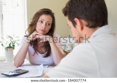 Young woman and man sitting with home bills at the table