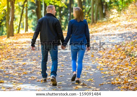 Young woman and man walking in city park holding hands