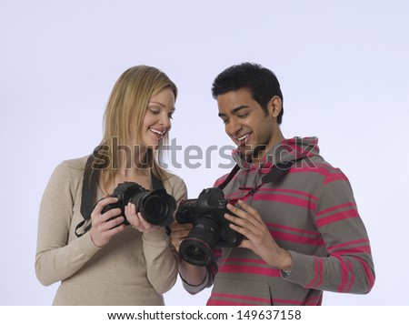 Young woman and man with digital cameras in studio - stock photo