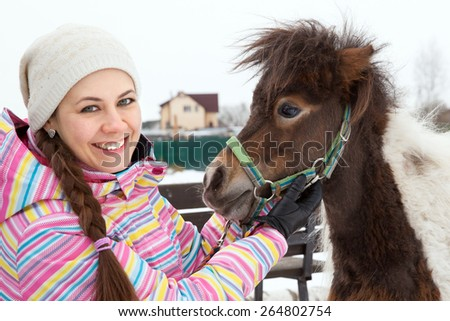 Young woman and miniature horse in winter park - stock photo