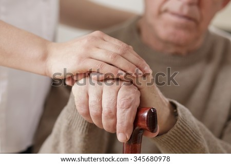 Young woman and old man holding hands - stock photo