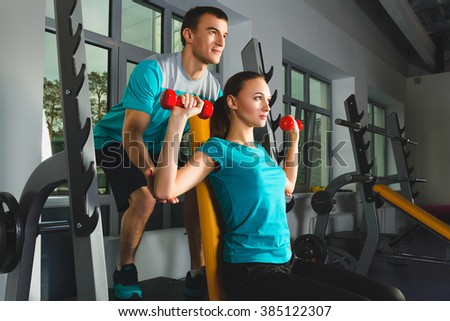 Young woman and personal trainer doing shoulders workout with dumbbells in a gym
