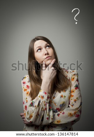 Young woman and question mark above head - stock photo