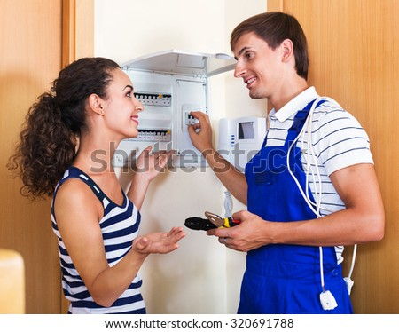 Young woman and repairman near electric meter in domestic interior