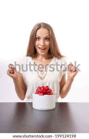 young woman and round gift box on the table, isolated on white