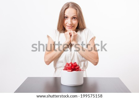 young woman and round gift box on the table, isolated on white - stock photo