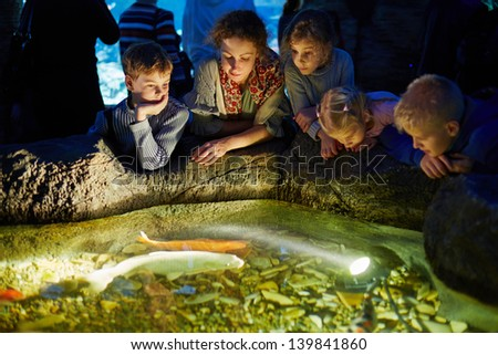 Young woman and several children look at fishes in enlighted pool at oceanarium - stock photo