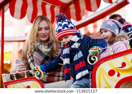Young woman and three sibling kids on a carousel, ferris wheel at Christmas funfair or market. Mother and two boys and girl, happy family having fun.