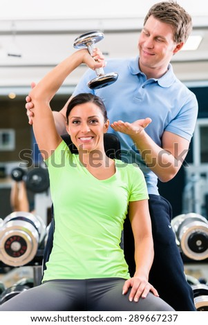 Young woman and trainer at exercise in gym with dumbbell weights