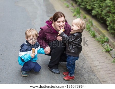 Young woman and two little boys having fun and eating ice cream, outdoors - stock photo