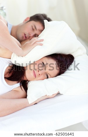 Young woman annoyed by the snores of her boyfriend in the bedroom at home - stock photo