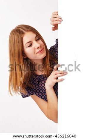 Young woman appear from the side of the billboard, looking at the billboard. - stock photo