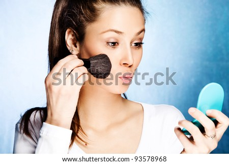 young woman apply blush with cosmetic brush hold small mirror n the other hand, studio shot