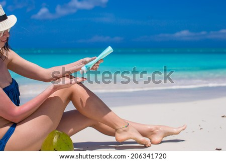 Young woman apply cream on her smooth tanned legs - stock photo