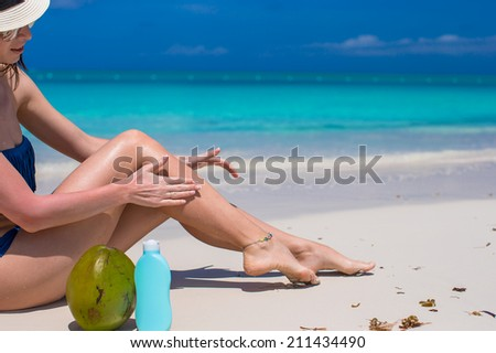Young woman apply cream on her smooth tanned legs at beach - stock photo